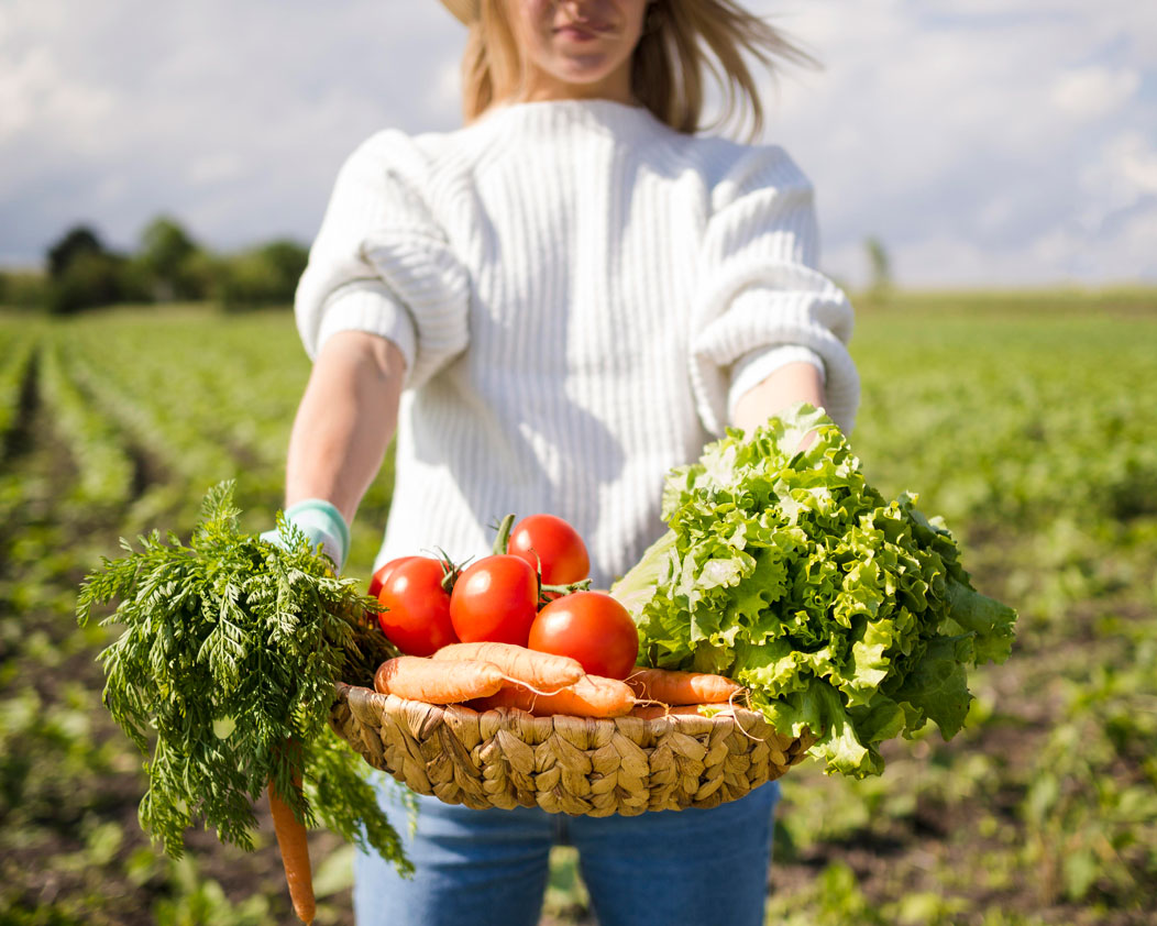 woman-holding-a-basket-full-of-vegetables-in-front-of-her
